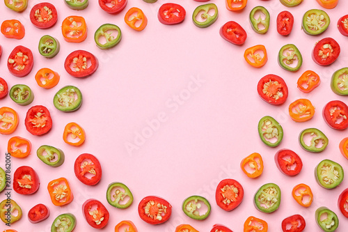 Fotobehang Hoogte schaal Frame made with different cut chili peppers on pink background, flat lay. Space for text
