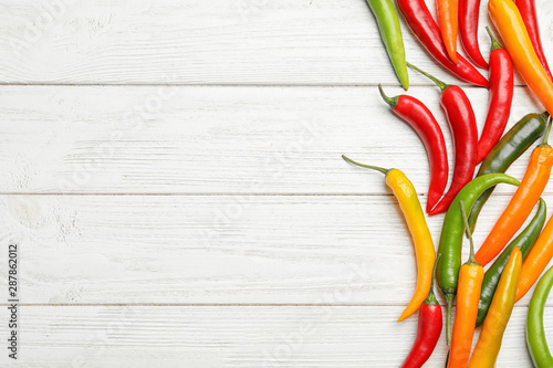 Different hot chili peppers on white wooden table, flat lay. Space for text