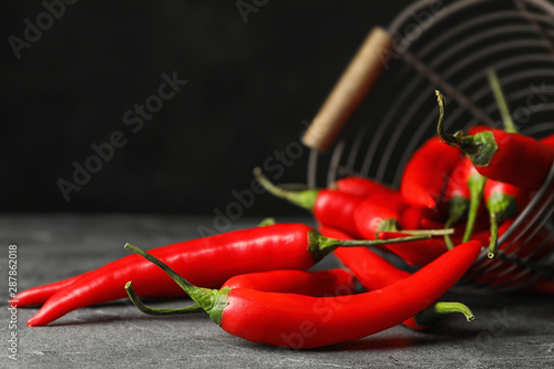 Foto auf Gartenposter Hot Chili Peppers Red hot chili peppers and metal basket on grey table, closeup. Space for text