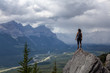 Adventurous Caucasian Girl is hiking up a rocky mountain during a cloudy and rainy day. Taken from Mt Lady MacDonald, Canmore, Alberta, Canada.