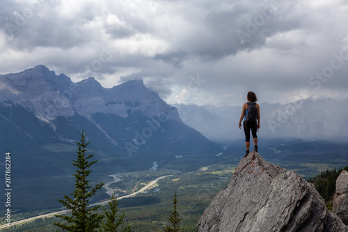 Fototapeta Adventurous Caucasian Girl is hiking up a rocky mountain during a cloudy and rainy day. Taken from Mt Lady MacDonald, Canmore, Alberta, Canada. obraz na płótnie