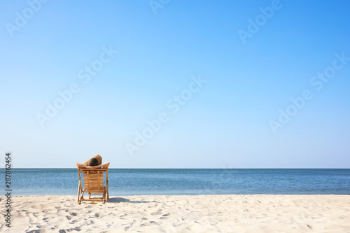 Fototapeta Young woman relaxing in deck chair on sandy beach