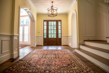 Grand And Elegant Yellow Entrance To A Home With Stairs. Oriental Rug A Wood And Glass Door.