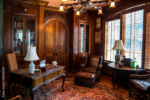 Fotografia, Obraz Dark stained wood stained home office with warm rust desert color with wood furn