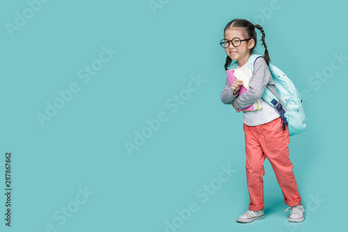 Obraz Beautiful smiling Asian little girl with glasses and hold a books with school bag is back to school, empty space in studio shot isolated on colorful blue background, Educational concept for school - fototapety do salonu