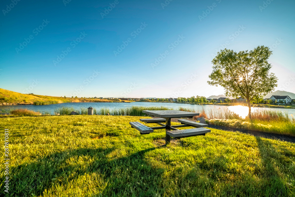 Fototapety, obrazy: Picnic table at a park with scenic view of a lake that reflects the sky and sun