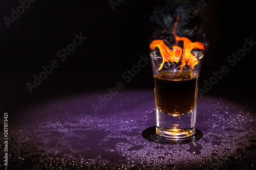 Hot alcoholic cocktail burning in shot glass. Tablou Canvas