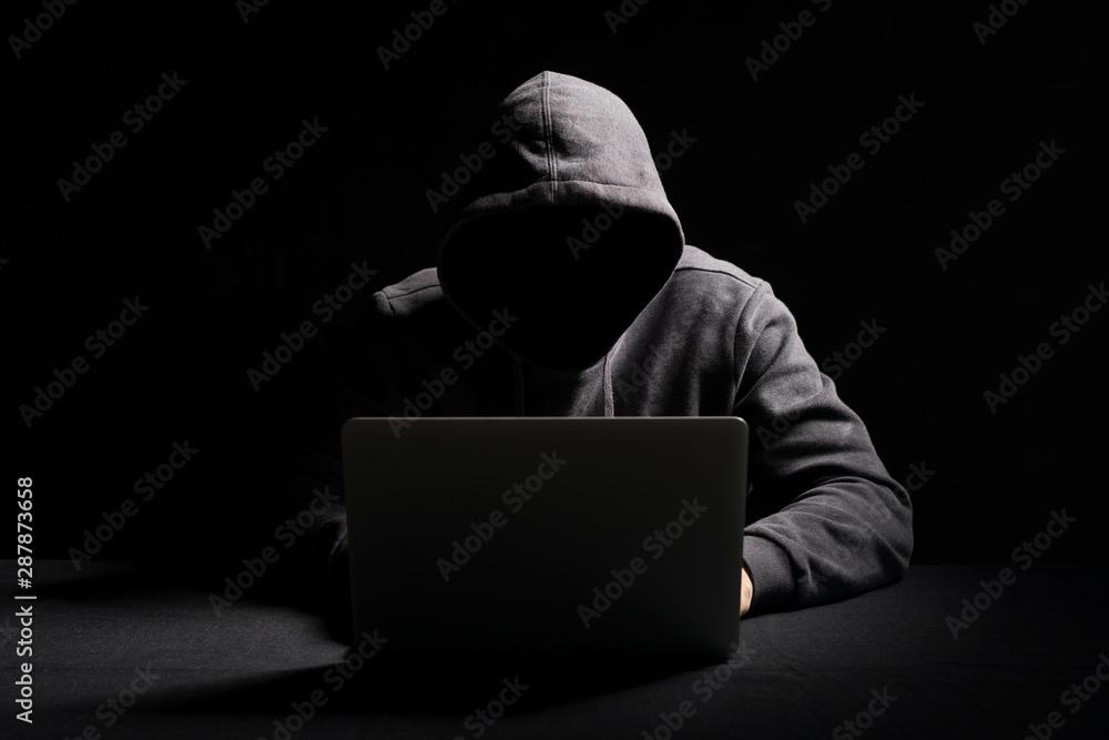 Fototapeta Hacker working on laptop in the dark