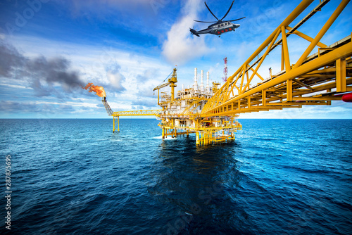 Fototapeta Offshore oil and gas rig platform with offshore helicopter transporting to oil rig at beautiful sky in the gulf of Thailand