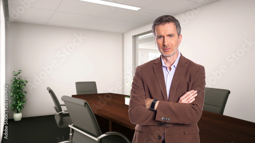 Obraz na plátně Middle-Aged businessman with gray hair and wearing a brown jacket standing in an office