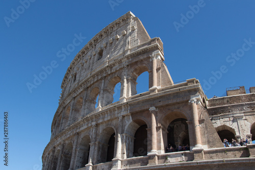 Fényképezés  Detailed view of Colosseum with blue sky on background, Rome, Lazio, Italy