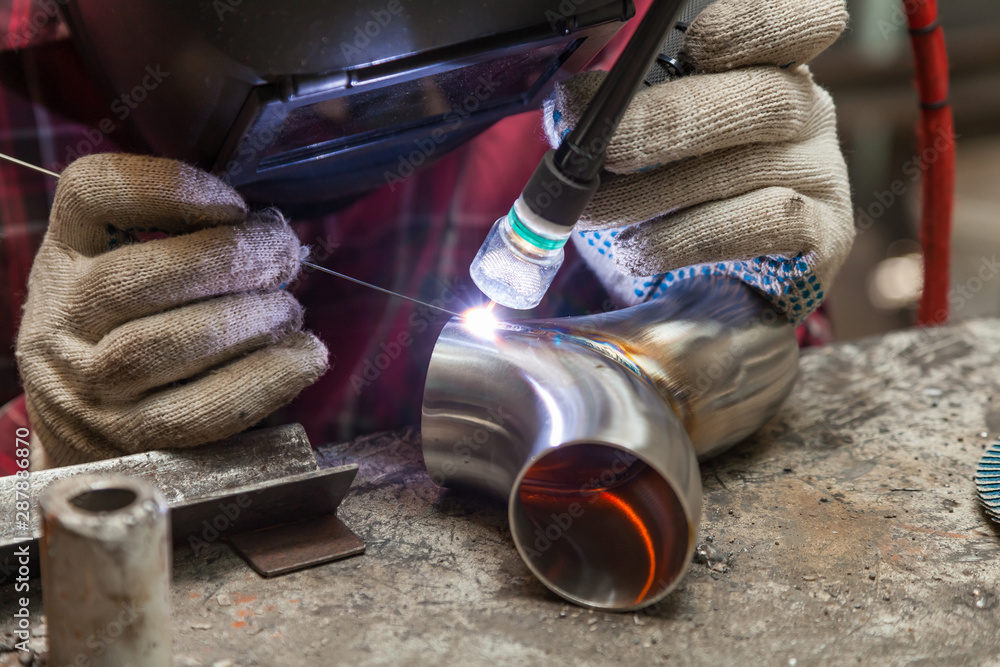 Fototapety, obrazy: Young guy welder in a checkered red shirt welds a stainless steel pipe using agronomic welding to protect his eyes with a mask in an iron workshop. Modern welding methods.