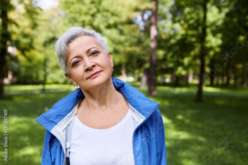 Portrait of happy senior Caucasian female with short gray hair relaxing in park, Wallpaper Mural