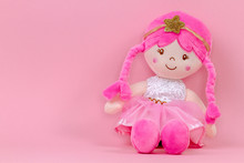 Stuffed Soft Doll Sitting On Pink Background
