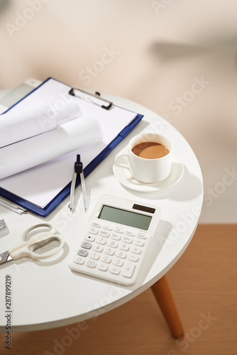 Top view of coffee notebook empty page, calculator, scissors on white table - 287899219