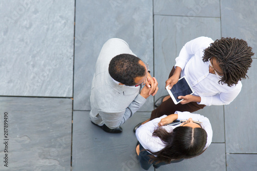 Photo sur Toile Les Textures Business team of three discussing work issues near office. Top view of business man and women standing outside, talking, gesturing and holding tablet with blank screen. Business team concept
