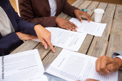 Fototapety, obrazy: Businesspeople discussing agreement terms. Business man and women sitting at cafe table, reading documents and drinking coffee. Paperwork concept