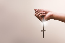 Praying Hands Hold A Crucifix Or Cross Of Metal Necklace With Faith In Religion And Belief In God On Confession Background. Power Of Hope Or Love And Devotion.