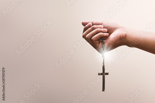 Obraz na płótnie Praying hands hold a crucifix or cross of metal necklace with faith in religion and belief in God on confession background