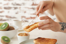 Woman Spreading Tasty Peanut Butter Onto Toasted Bread, Closeup