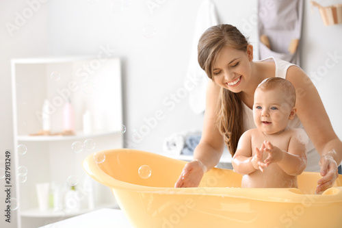 Obraz Mother bathing her cute little baby at home - fototapety do salonu
