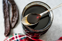 Carob Molasses Dripping From Spoon To Jar.