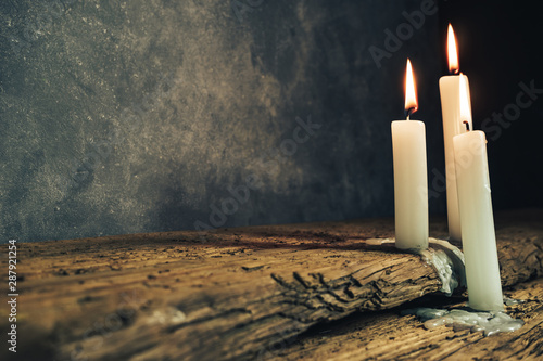 Pinturas sobre lienzo  Close up beautiful burned candles on a old oak wooden table and dark gray wall background