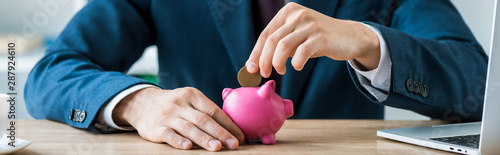 Cuadros en Lienzo  panoramic shot of businessman putting metallic coin into piggy bank near laptop
