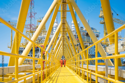 Fototapeta Worker walking at the connection bridge between quarter platform and oil and gas central processing platform, offshore oil and gas operation business. obraz