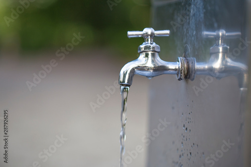 Fototapeta Water tap with water drop outdoor green park background