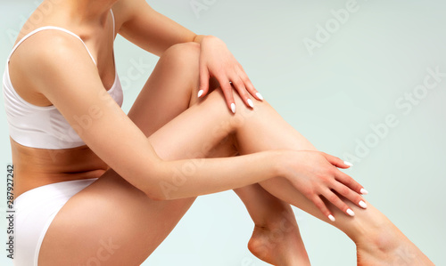Wellness and beauty concept, beautiful slim woman in white underwear lingerie touches her smooth legs