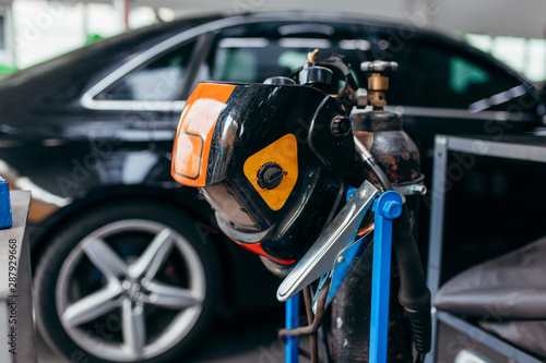 Welding equipment close up in a car repair station on car background Canvas Print