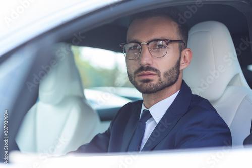 Obraz na plátně  Handsome bearded man wearing glasses sitting in car