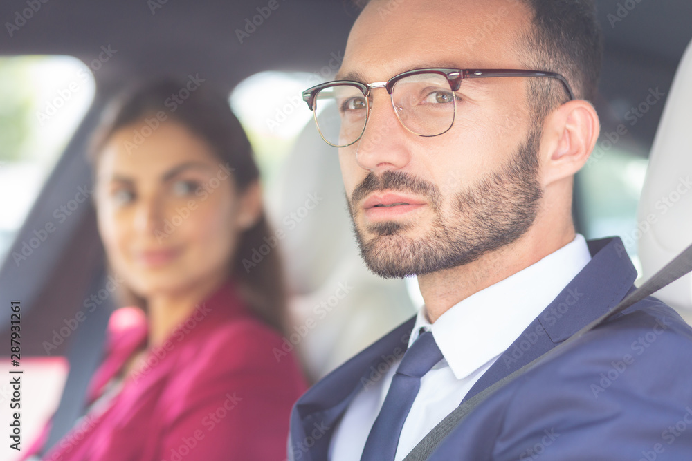 Bearded young man wearing glasses sitting near wife in car