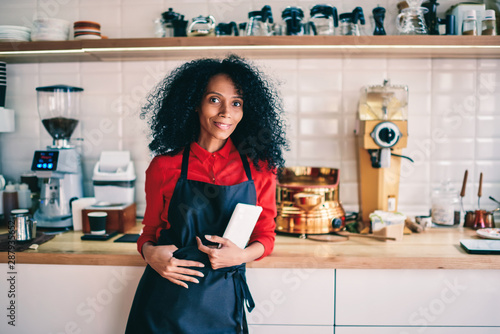 Fotomural  Portrait of successful female barista in black apron holding modern touch pad device and smiling at camera standing on working place in own coffee shop