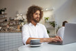 Indoor portrait of pretty young curly man with beard reading good news on his laptop, working in city cafe remotely, wearing white shirt
