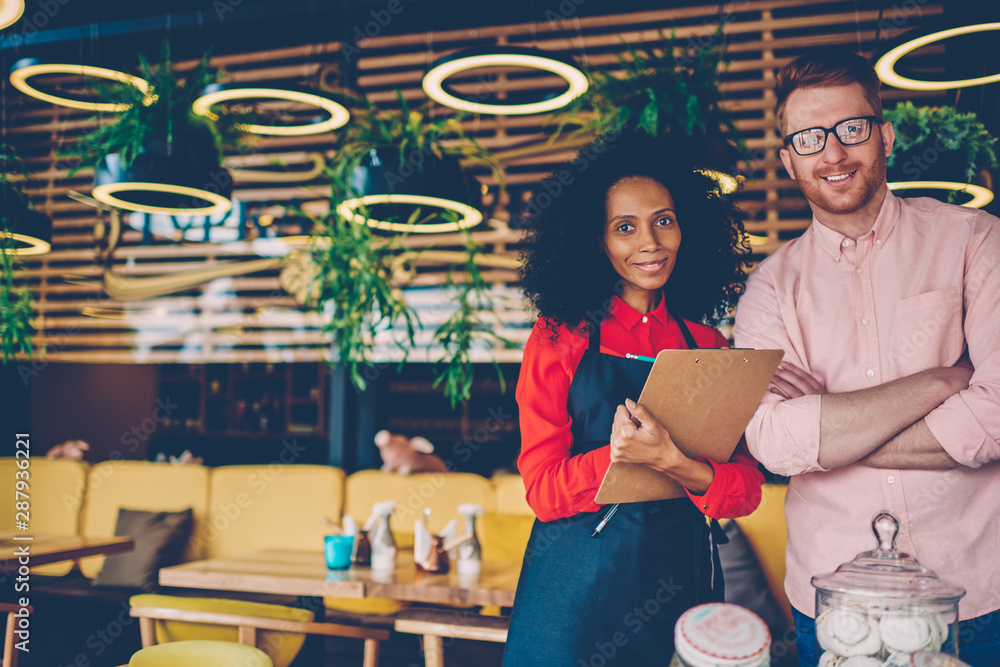 Fototapeta Portrait of successful partnership of african american professional barista with experienced caucasian manager on development common business.Owner of cafe and waitress with menu smiling at camera