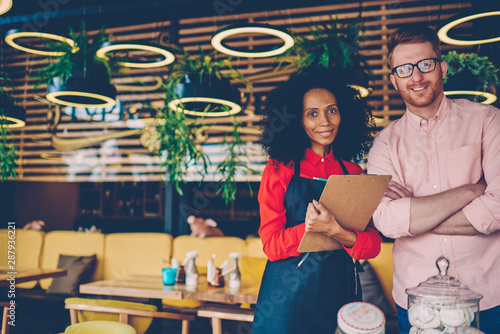 Portrait of successful partnership of african american professional barista with experienced caucasian manager on development common business Wallpaper Mural