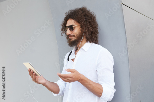 Fototapeta  Outdoor shot of lovely young man with beard and curly hair, wearing sunglasses a