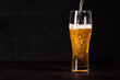canvas print picture - Pour beer in beer glass on dark wooden background. October fest background