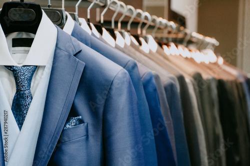 Men suit jackets on hanger in a shop