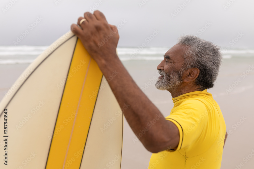 Fototapety, obrazy: Senior male surfer standing with surfboard on the beach