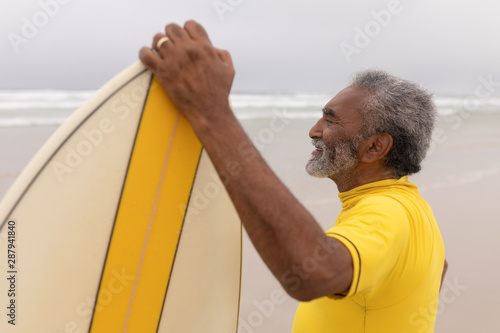 Senior male surfer standing with surfboard on the beach Canvas Print