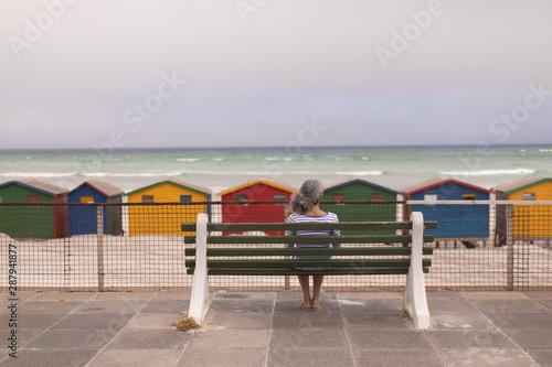 Senior woman sitting on promenade bench at beach