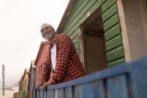 Senior man looking away while standing at beach hut
