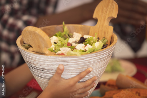 Boy holding wooden salad bowl at dining table