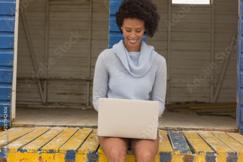 Young African American woman using laptop at beach hut