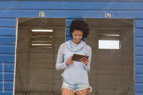 Young African American woman using digital tablet at beach hut