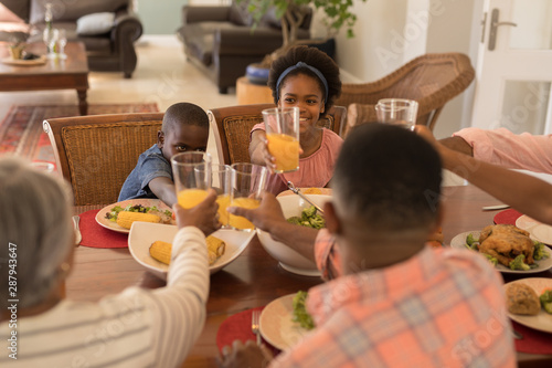 Multi-generation family toasting glasses of orange juice on dining table