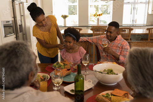 Mother wiping daughter mouth with napkin after meal on dining table